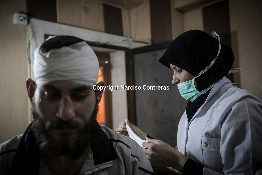 Hannah, a 25 years old nurse, bandages the head of an apposition fighter injured by an airstrike attack as she works full time at one hospital in an undisclosed location inside the rebel controlled area of the northern Syrian city of Aleppo.