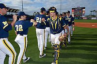 Michigan Wolverines catcher Harrison Wenson (7) celebrates with teammates, including Joe Pace (32), Evan Hill (21), and Jayce Vancena (20) after the second game of a doubleheader against the Canisius College Golden Griffins on February 20, 2016 at Tradition Field in St. Lucie, Florida.  Michigan defeated Canisius 3-0.  (Mike Janes/Four Seam Images)