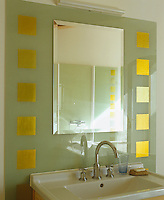 One of a pair of wash basins in the bathroom has a wall-mounted mirror surrounded by glass decorated with squares of gold leaf