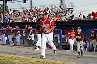 "Batavia Muckdogs first baseman Eric Gutierrez (43) takes the field with a young ""Stars of the Game"" participant before a game against the Brooklyn Cyclones on July 4, 2016 at Dwyer Stadium in Batavia, New York.  Brooklyn defeated Batavia 5-1.  (Mike Janes/Four Seam Images)"