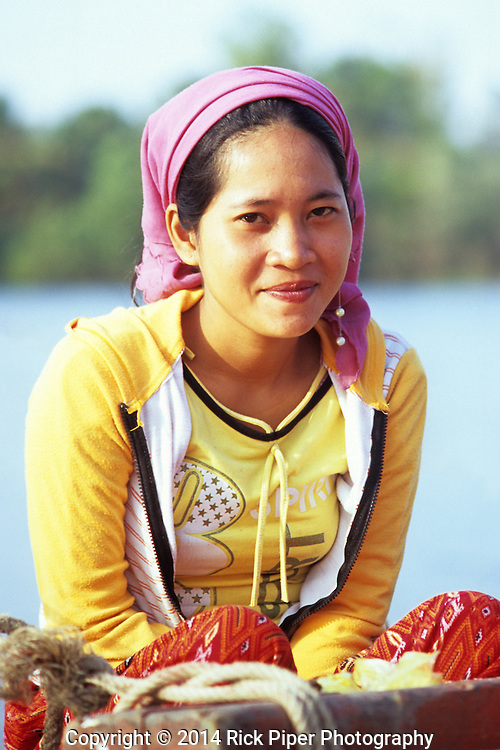 Young smiling Cham woman, wearing colourful clothing and mauve headscarf, sitting in a fishing boat on the Sanke river, Kampot, Cambodia.