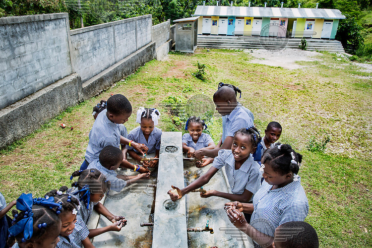 On 'Global Handwashing Day' pupils at a school in Camp Perrin try out the newly built safe water facility financed by the Belgian NGO PROTOS. The pupils have been taught how important it is to always wash their hands after each visit to the toilet. In 2011, according to WHO and UNICEF, only 48 percent of the rural population had access to drinking water and only 29 percent had sanitation facilities.