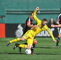 Eddie Gaven (12) of The Columbus Crew gets fouled by Perry Kitchen (23) of D.C. United. The Columbus Crew defeated D.C. United  2-1, at RFK Stadium, Saturday March 23, 2013.
