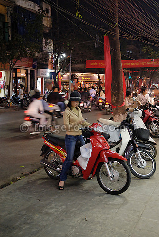 Asia, Vietnam, Hanoi. Hanoi old quarter. Using a mobile phone while being on the motorbike.