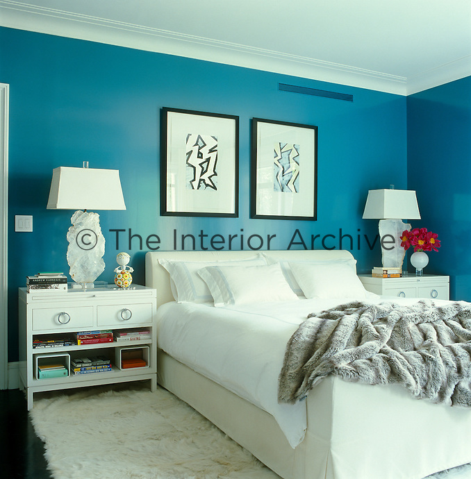 In the master bedroom a pair of framed prints by Chuck Price hangs on the deep turquoise walls above the Richard Mishaan designed bed and bedside tables