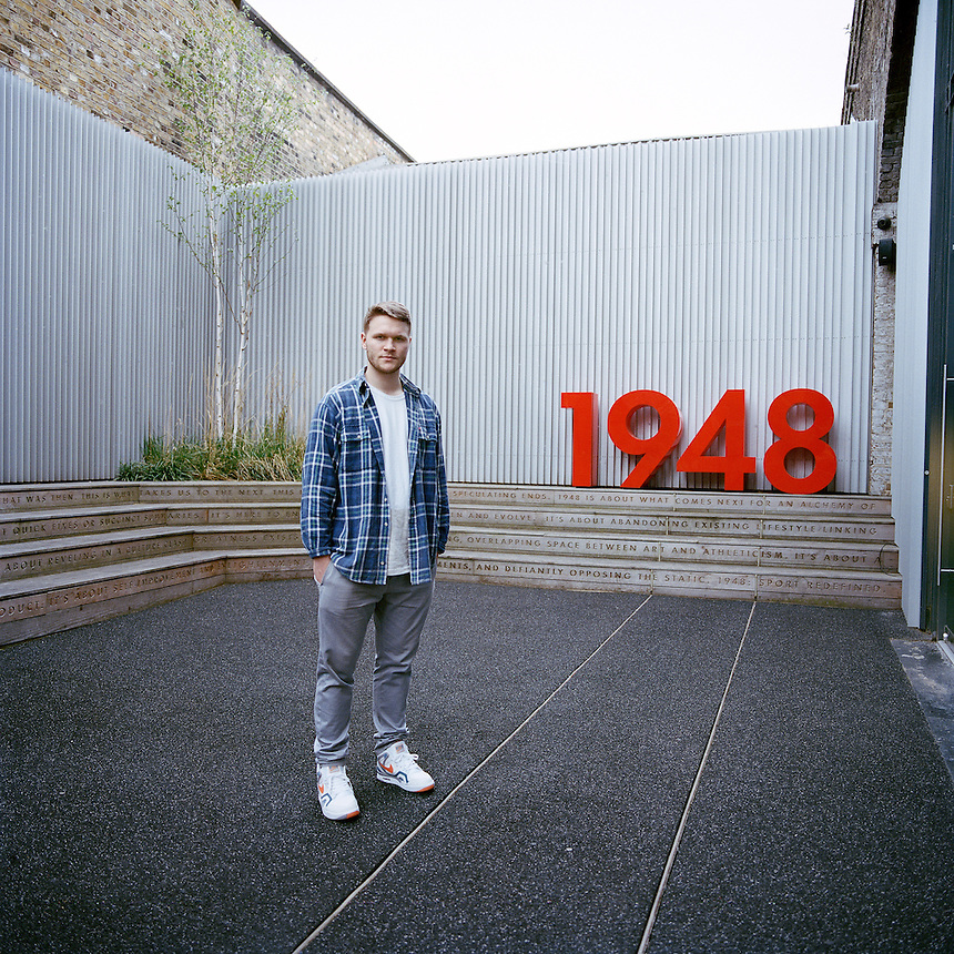 Trainer collector, Ronan Walsh stands outside the Nike exhibition store 1948 where he works.<br /> Ronan wears a pair of Nike Air Tech Challenge II - Clay Blue kicks.<br /> Shoreditch, London, 2014.