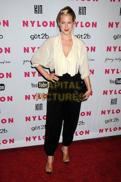 LAURA RAMSEY.Nylon Magazine's Young Hollywood Party held at the Roosevelt Hotel's Tropicana Bar, Hollywood, California, USA..May 12th, 2010.full length black harem trousers brown ankle boots shoes open toe white cream top hand on hip sheer blouse clutch bag .CAP/ADM/BP.©Byron Purvis/AdMedia/Capital Pictures.