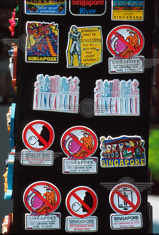 Pin badges for sale, making light of the severe laws and regulations regarding public behaviour in Singapore. Chewing gum, for example, can result in a $1000 fine.