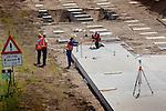UTRECHT - Op knooppunt Oudenrijn plaatsen medewerkers van Heijmans Infrastructuur betonkoppen op de onlangs geslagen heipalen als onderdeel van een nieuw, experimenteeel wegdek, ModieSlab. Het door Heijmans Infrastructuur, Betonson en ingenieursbureau Arcadis ontwikkelde asfalt bestaat uit een prefab-betonplaat met een toplaag van 'zeer open cement beton' die op een fundering van palen wordt gelegd.  Het wegvak wordt als proef aangelegd in opdracht van Rijkswaterstaat's project Wegen naar de Toekomst, en moet aantonen dat snelwegen niet alleen sneller kunnen worden aangelegd maar eveneens geluidsstilller.COPYRIGHT TON BORSBOOM