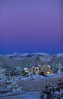 Light bounces off windows of a mountain house at sunrise.