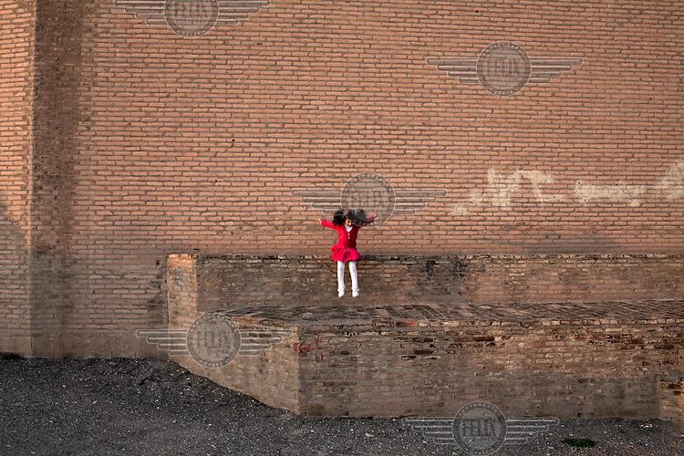 A girl jumps from a ledge in front of  the Citadel in Erbil on a friday afternoon. The Citadel is an inhabited mound in the centre of the modern Iraqi city of Erbil, which is said to be one of the oldest, continually inhabited places in the world. Earliest traces of habitation on the mound date back to the 5th millennium BC, possibly earlier.