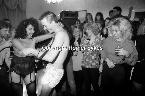Surprise Stripogram girl for a birthday present. Mans birthday party surprise present get her clothes off. Colleagues all having fun. South London pub. 1991