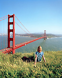 USA, California, Marin Headlands, woman looking at Golden Gate Bridge and San Francisco while relaxing
