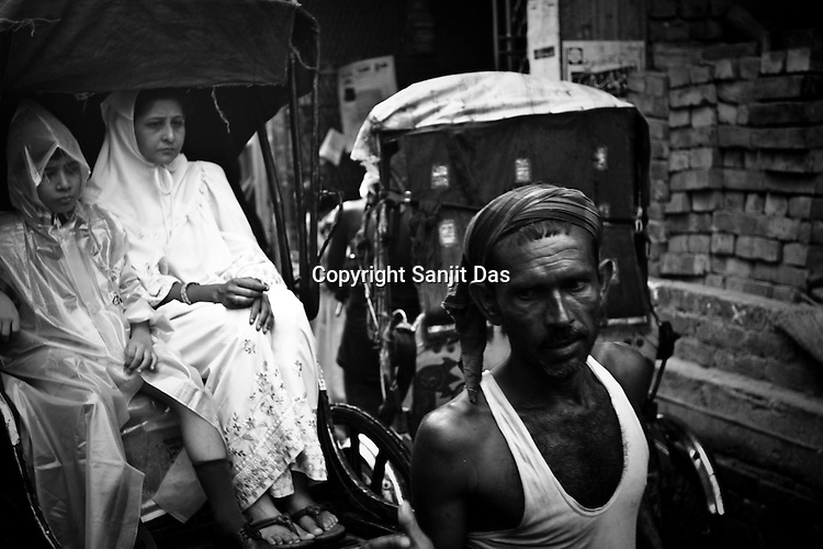 A rickshaw puller takes a women and a school boy through the monsoon rain in Calcutta, India. 93 out of every 100 rickshaw pullers are homeless. They sleep after the city sleeps and wake up before everyone else does. Many of them are the sole bread earners for their family. Many plus 40. Many minus any other specialisation for any other job. Of the twenty four thousand rickshaw pullers, only 387 have licenses. .Many rickshaw pullers earn a meagre wage of 100-150 rupees (US $ 2.25-3.5) a day of which they have to give a daily rickshaw rent of 60 (US$ 1.35) rupees to the agent at the end of the day.