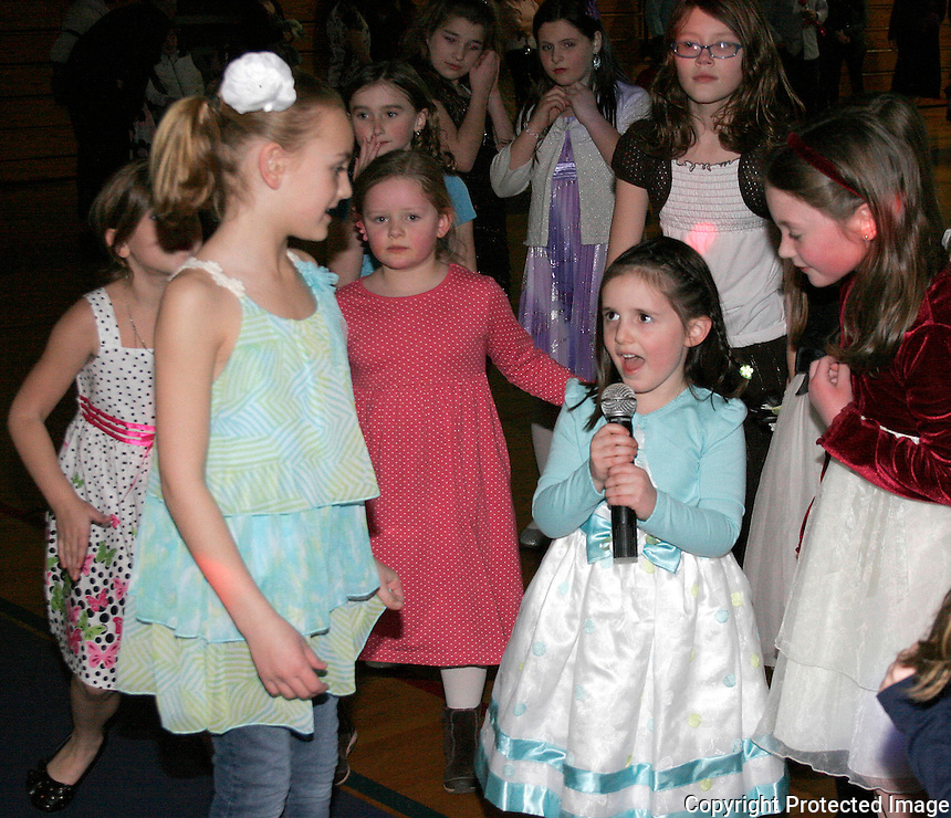 Jordan Robbins age 8 sings to her classmates during the Snowflake Social Dance on Friday, show their dance skills, at the Norwood Middle School in Norwood. The Snowflake Social was formerly called the Father/Daughter - Mother/Son Dance.(Photo by Gary Wilcox)