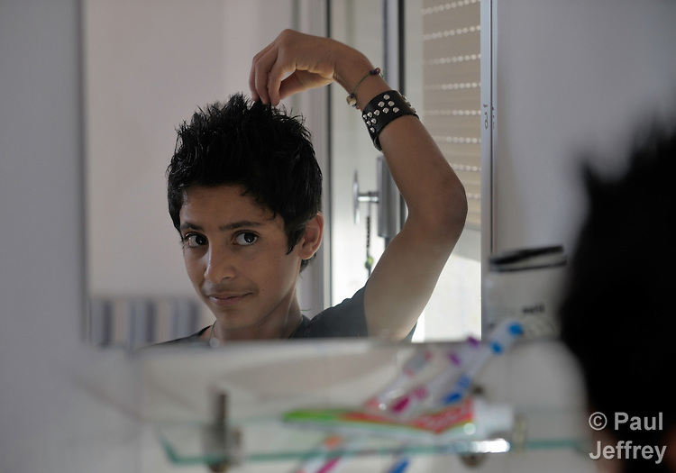 Mohamen Marzok, a 15-year-old Iraqi refugee, fine tunes his hair in his family's room in a shelter outside Beirut for Iraqi refugees and other residents of Lebanon who have suffered from domestic violence. The shelter, a program of the Caritas Lebanon Migrant Center, which is funded by Catholic Relief Services, the relief and development agency of the U.S. Catholic community, is located in an unnamed community on the outskirts of Beirut.