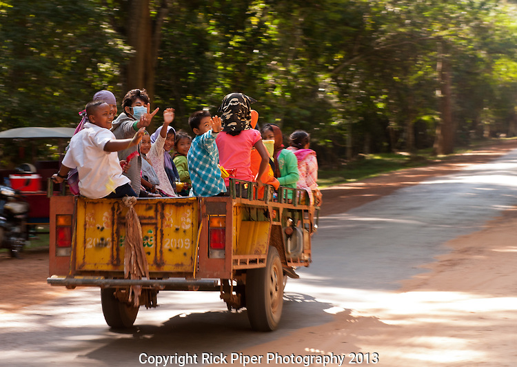 Passengers - Travelling to work and school on a remork-moto, early morning at Angkor Thom North Gate, Angkor, Cambodia