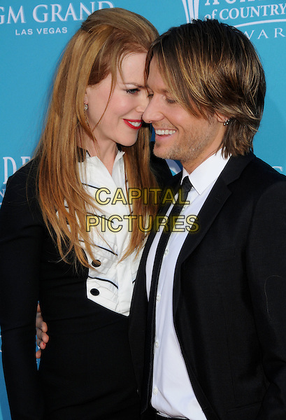 NICOLE KIDMAN & KEITH URBAN.Arrivals - 45th Annual Academy Of Country Music Awards held at the MGM Grand Garden Arena, Las Vegas, NV, USA, 18th April 2010..ACM ACMs half length red lipstick make-up black bib front white shirt buttons collar smiling married husband wife couple arm around profile smiling shirt tie suit dress.CAP/ADM/BP.©Byron Purvis/AdMedia/Capital Pictures.
