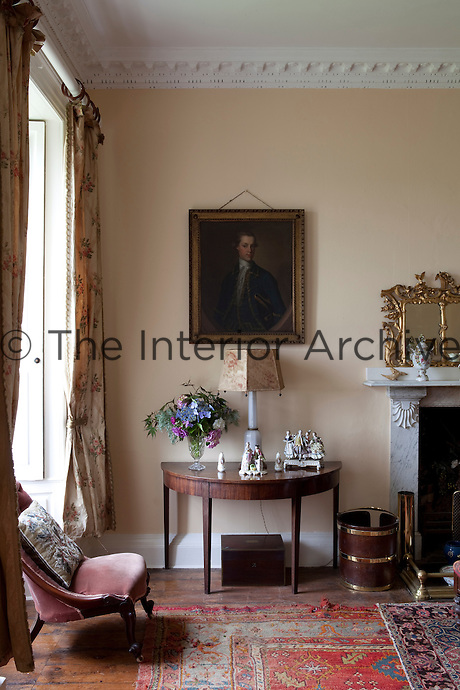 Antique furniture in the drawing room is arranged around an elegant marble fireplace