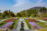 "Italy, Piedmont, Verbania: Villa Taranto - Botanical Garden, terraced garden with bronze statue ""The Fisher"" by Vincenzo Gemito, at background Villa Taranto, prefecture of province Verbano-Cusio-Ossola 
