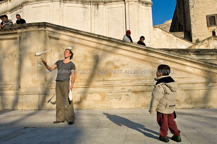 2/26/2006--Avignon, France..A juggler from Avignon entertains visitors outside the Palais des Papes. The cultural capital of southern France, Avignon is home to an elaborate international theater, dance, and music festival, which this year will run from July 6 to 27. It is a haven that draws theatergoers-young and old-from around the world, serving up an elaborate menu of stage work, both traditional and avant-garde. But culture abounds in this city throughout the year, at the opera, the music halls, and at an array of museums..Photograph By Stuart Isett.All photographs ©2005 Stuart Isett.All rights reserved.