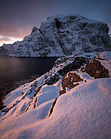 Winter sunser over snow covered coast at Å, Moskenesøy, Lofoten Islands, Norway