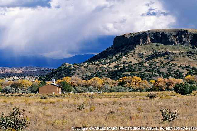 Black Mesa looms over an old church during an autumn storm at San Ildefonso Pueblo in Northern New Mexico near the village of Pojoque
