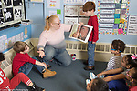 Education Preschool classroom scenes 4-5 year olds female teacher reading book to group at circle time