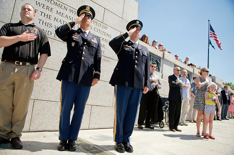 UNITED STATES - JUNE 6: Capt. Ted Randall, center, Chaplain at Arlington National Cemetery, Ryan Cook, left, Assistant Chaplain, and Pfc. Victor Roselli, listen to the National Anthem during a ceremony at the World War II Memorial on the Mall to mark the 70th anniversary of D-Day. (Photo By Tom Williams/CQ Roll Call)