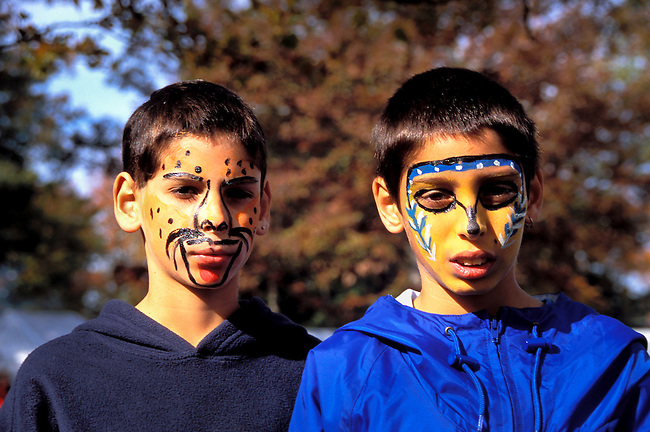 Creek boys, who are brothers, with painted faces attend a pow wow festival in the Northeast