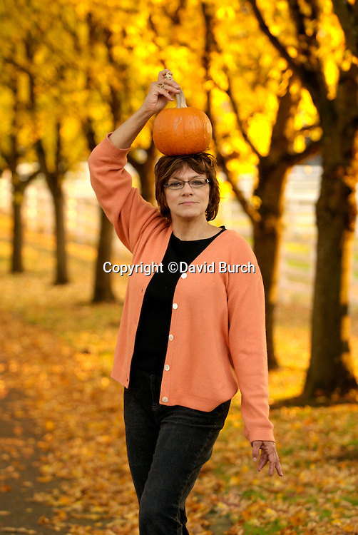 Woman having fun posing with pumpkin on her head in Autumn scene