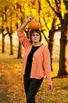 Woman having fun posing with pumpkin on her head in Autumn scene