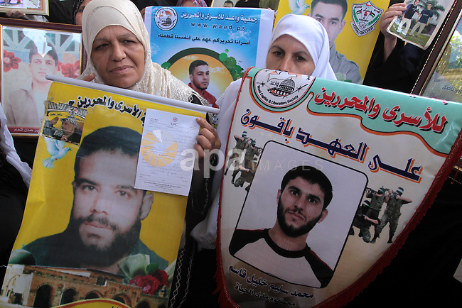 Palestinian women hold pictures of jailed relatives during a protest calling for the release of Palestinian prisoners from Israeli jails at the Red Cross office in Gaza City on Sept 27,2010 . Photo by Mohammed Asad