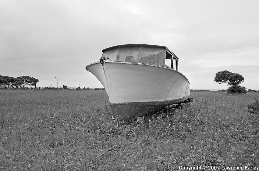 "A workboat being repaired in a field beside a house is a common sight on Harkers Island.  Boatbuilders prided themselves on being ""backyard"" boatbuilders.  When she was finished, the boat was moved to the shoreline and launched."