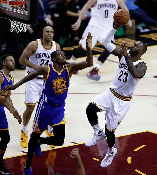 JGM151 CLEVELAND (ESTADOS UNIDOS) 08/06/2017.- El jugador de los Cavaliers LeBron James (d) salta para encestar ante la mirada de Kevin Durant (c) de los Warriors durante el tercer partido de las Finales de la NBA que enfrentó a los Warriors de Golden State contra los Cavaliers de Cleveland en el Quicken Loans Arena en Cleveland, Ohio (Estados Unidos) ayer, 7 de junio de 2017. EFE/Larry W. Smith