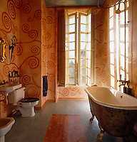 The painted bathmat on the floor of the bathroom in David Carter's Normandy house is painted in a floral design to match the swirls of the vivid orange mural