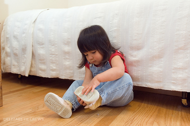 Berkeley CA Girl, Guatemalan, two-years-old, trying to figure out how to put on shoe  MR