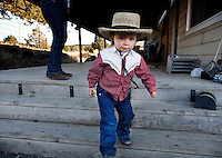 Dressed in her straw hat and western shirt, a little as a cowgirl, 2 1/2 years old heads out to the barn to see watch the horses.<br />