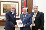 Palestinian President Mahmoud Abbas rceives the annual report of the Palestinian International Cooperation Agency of 2018 from the Palestinian foreign Minister Riyad al-Maliki, in the West Bank city of Ramallah, August 18, 2019. Photo by Thaer Ganaim