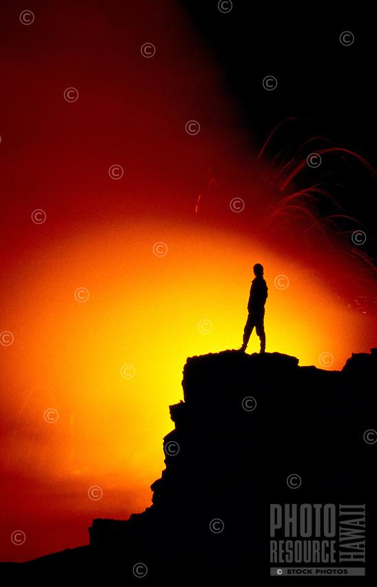Man watching lava spill into the sea from Kilauea Volcano, Hawaii volcanoes national park, Big island of Hawaii