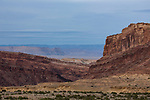 Layered sandstone formations  make up the rugged San Rafael Reef on the eastern edge of the San Rafael Swell in south central Utah.  In the distance are the Book Cliffs and Battleship Butte.