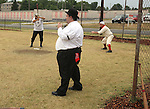 """The arbiter -- """"Judge"""" David P. Showmaker (center) -- was the forerunner of the modern baseball umpire.  Here, he watches the play of the game from a few yards away during a vintage base ball game on August 4, 2012 at the Swansea Moose Lodge fields between the Belleville Stags and the St. Louis Unions.  At left is Matt """"Mayhem"""" Moushey of the Unions, center is arbiter Showmaker, and at right is the """"behind"""" (or catcher) Mike """"Mule"""" Garrett of Belleville."""