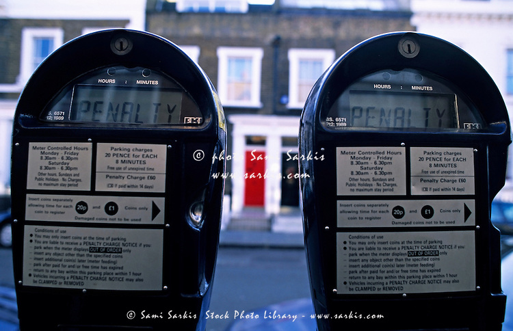 Two parking metres side by side in a street, London, England, UK.