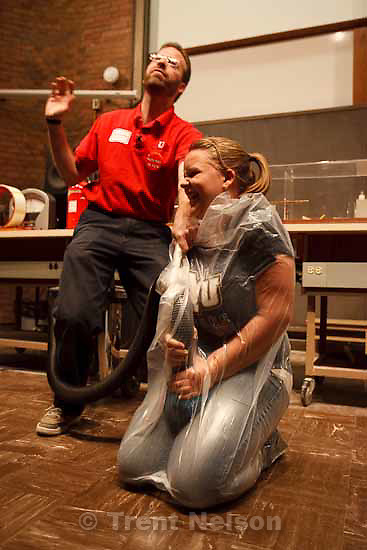 Adam Beehler (left), tells Centerville Junior High School student Kimberly Paulsen to try to stand up or wave while she is wrapped in plastic with a vacuum sucking out the air inside. Beehler, a Lecture Demonstrator for the Department of Physics at the University of Utah, put on a show for middle and high school students attending Science day at the University Saturday, November 7 2009.