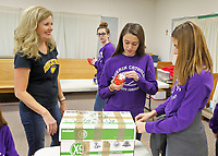 Guerin students helped fill food boxes at St. Maria Goretti for distribution at Thanksgiving.  (L-R) Michelle Craddick, a volunteer at SMG and Gabriela Peabody and Grace Mehne.