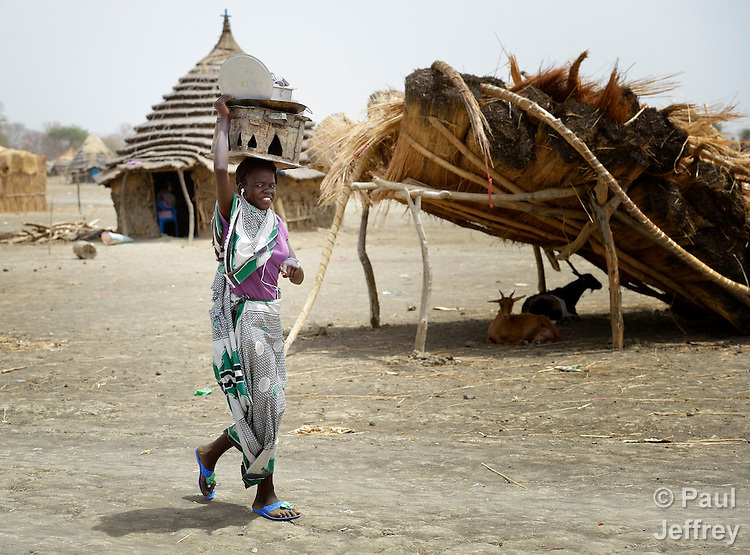 A displaced woman walks in Agok, a town in the contested Abyei region where tens of thousands of people fled in 2011 after an attack by soldiers and militias from the northern Republic of Sudan on most parts of Abyei. Although the 2005 Comprehensive Peace Agreement called for residents of Abyei--which sits on the border between Sudan and South Sudan--to hold a referendum on whether they wanted to align with the north or the newly independent South Sudan, the government in Khartoum and northern-backed Misseriya nomads, excluded from voting as they only live part of the year in Abyei, blocked the vote and attacked the majority Dinka Ngok population. The African Union has proposed a new peace plan, including a referendum to be held in October 2013, but it has been rejected by the Misseriya and Khartoum. The Catholic parish of Abyei, with support from Caritas South Sudan and other international church partners, has maintained its pastoral presence among the displaced and assisted them with food, shelter, and other relief supplies.