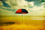 An umbrella standing on a sandy beach
