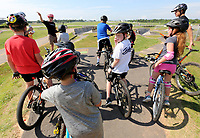 NWA Democrat-Gazette/DAVID GOTTSCHALK Staff members and campers review track features Monday, July 8, 2019, during the Breakaway Cycling Team Bike Skills Training Camp at the Runway Bike Park at the Jones Center in Springdale. The two day camp emphasizes skills, etiquette and safety. Today the campers will be on the Greenway Trail System.