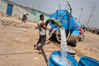 A Peruvian water distribution worker with a hose splashes drinking water from a truck into plastic barrels on the dusty hillside of Pachacútec, a desert suburb of Lima, Peru, 20 January 2015. Although Latin America (as a whole) is blessed with an abundance of fresh water, having 20% of global water resources in the the Amazon Basin and the highest annual rainfall of any region in the world, an estimated 50-70 million Latin Americans (one-tenth of the continent's population) lack access to safe water and 100 million people have no access to any safe sanitation. Complicated geographical conditions (mainly on the Pacific coast), unregulated industrialization (causing environmental pollution) and massive urban poverty, combined with deep social inequality, have caused a severe water supply shortage in many Latin American regions.
