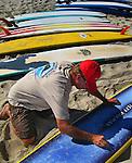 A man waxes down  a collection of surfboard on Kailua beach of Hawaii.